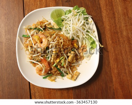 Fried vermicelli Thai style with prawns, Stir fry noodles with shrimp in padthai style on wood table.