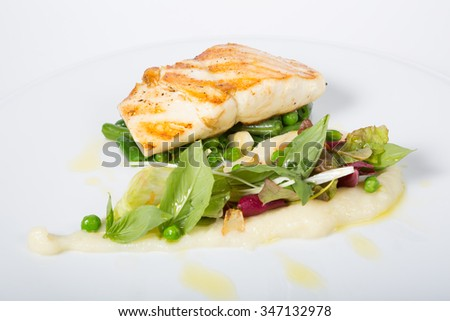 Fried white fish fillet with garnish - stock photo
