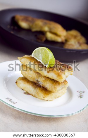 Fried white fish on a plate with lime