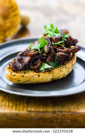 Fried wild mushrooms on toasted bread, served on a tin plate.