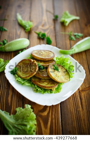 fried zucchini fritters with dill on a plate - stock photo
