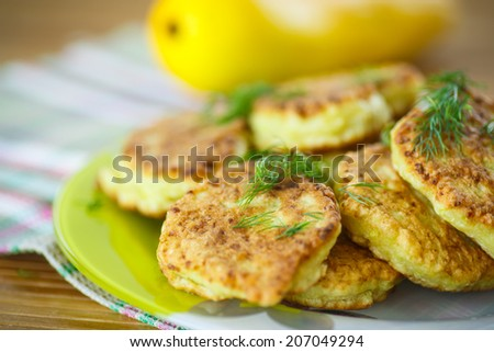 fried zucchini pancakes with dill on a plate - stock photo