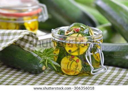 Fried zucchini slices pickled in olive oil with herbs and filled in a canning jar - stock photo