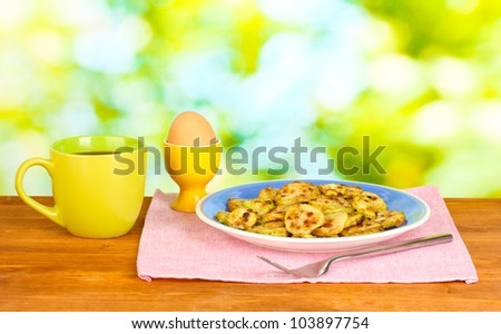 Fried zucchini with eggs and coffee for breakfast on wooden table on green background