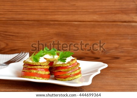 Fried zucchini with fresh tomatoes, yoghurt and green parsley. Delicious vegetable appetizer on plate and on wooden background. Easy zucchini snacking for summer - stock photo