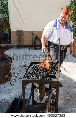 Friedberg, Germany - July 09, 2016: A man dressed in traditional costume is working as a blacksmith in the traditional way of the eighteenth century on the historic festival Friedberger Zeit (Time of