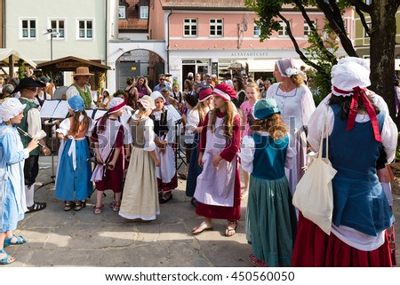 Friedberg, Germany - July 09, 2016: People mainly dressed in traditional costumes of the eighteenth century are watching children about to perform authentic songs on the historic festival Friedberger