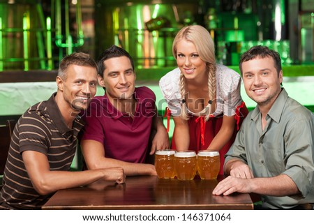 Friend at the beer festival. Three cheerful male friends and waitress in traditional German costume looking at camera and smiling - stock photo