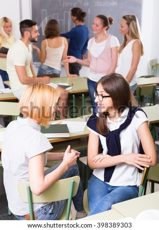Friendly adult students chatting while sitting in the university