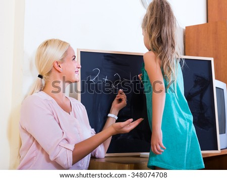 Friendly adult woman introducing numbers to small girl at home