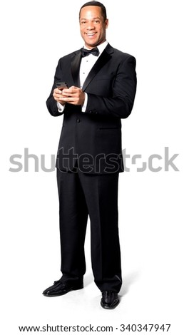 Friendly African man with short black hair in evening outfit using mobile phone - Isolated