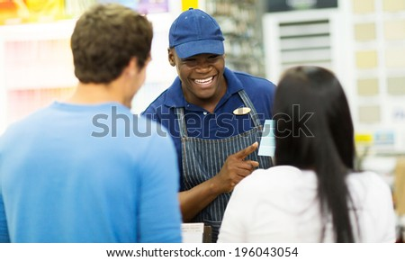 friendly african shop assistant helping couple choose paint color at hardware store - stock photo