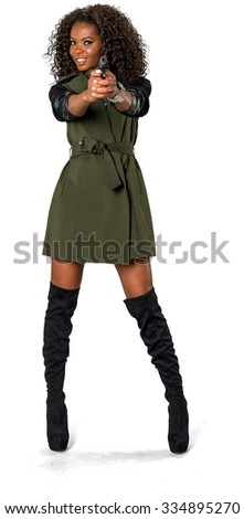 Friendly African woman with medium dark brown hair in casual outfit using handgun - Isolated - stock photo