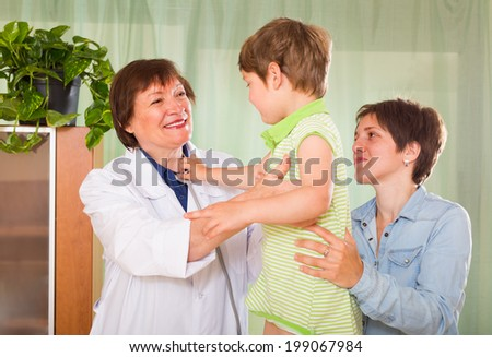 Friendly aged female pediatrician doctor examining preschooler at clinic  - stock photo