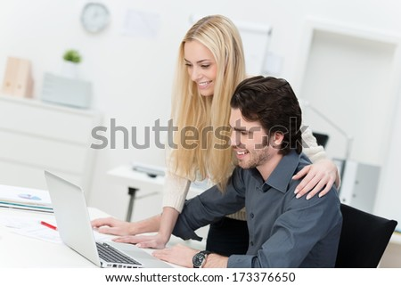 Friendly and happy male and female co-workers working at the office on a laptop - stock photo