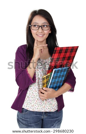 Friendly Asian teacher holding some books, smiling and looking to her side imaginatively, isolated on white background - stock photo