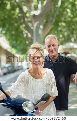 Friendly attractive middle-aged blond woman holding a scooter in a tree lined street as her husband stands behind her with a smile