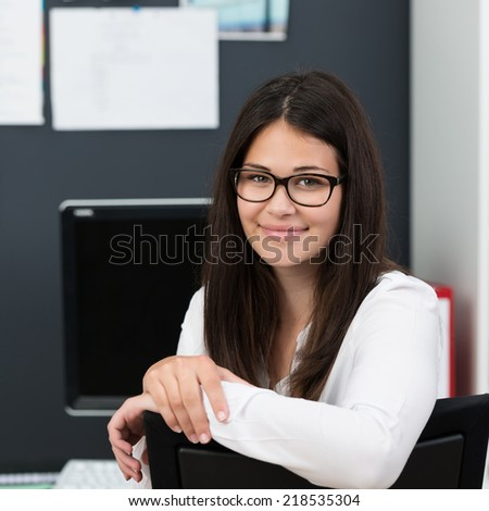 Friendly attractive young businesswoman wearing glasses leaning over the back of her chair at the office to smile at the camera - stock photo