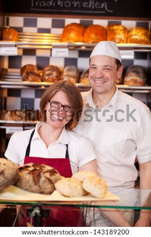 Friendly bakery staff standing behind the counter in a modern bakery with well stocked shelves - stock photo