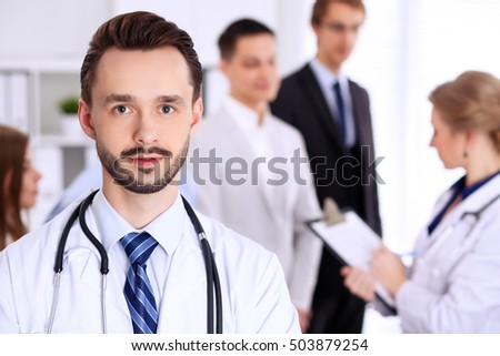 Friendly bearded male doctor with patients