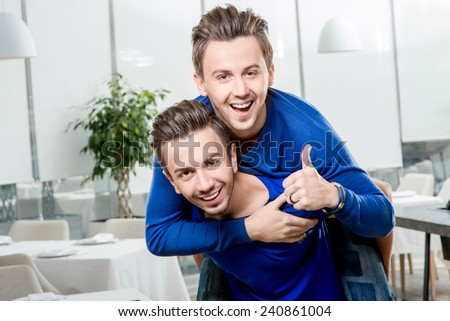 Friendly brothers twins having fun riding piggyback in the white home or restaurant interior. Family relationship between two brothers - stock photo