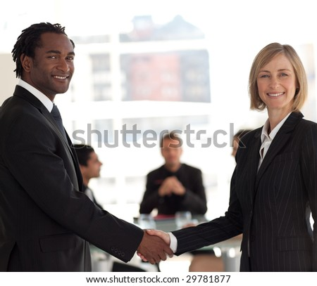Friendly Business handshake in front of workgroup - stock photo