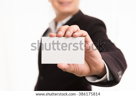 Friendly business man holding a business card and smiling
