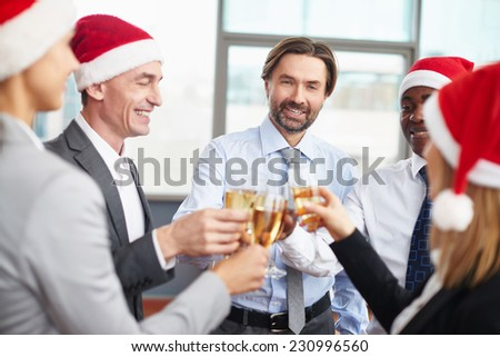 Friendly business partners in Santa caps toasting with champagne at corporate party - stock photo