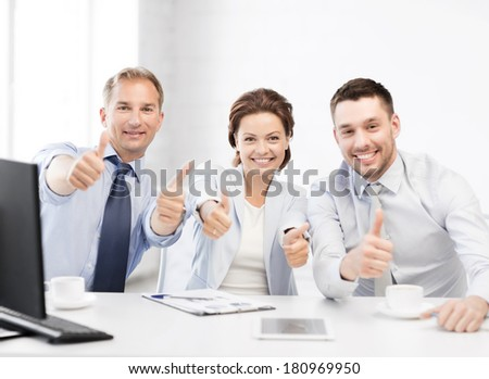 friendly business team showing thumbs up in office - stock photo