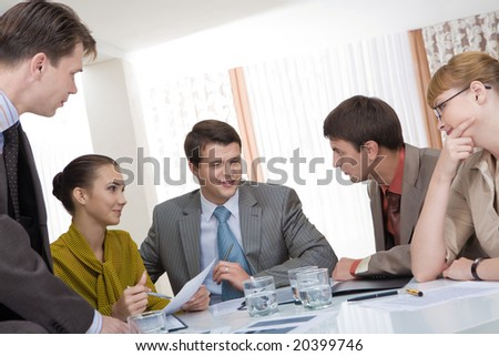 Friendly business team sitting around table and talking about new ideas