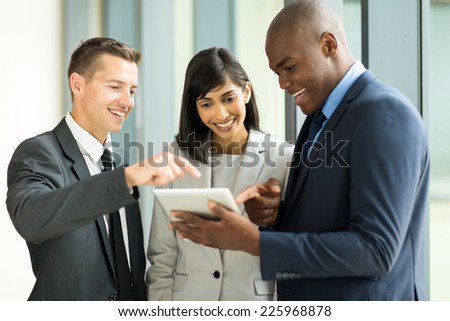 friendly business team using tablet computer in office - stock photo