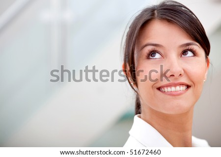 Friendly business woman smiling and looking up in her office - stock photo