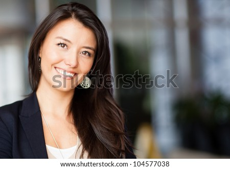 Friendly business woman smiling at the office - stock photo