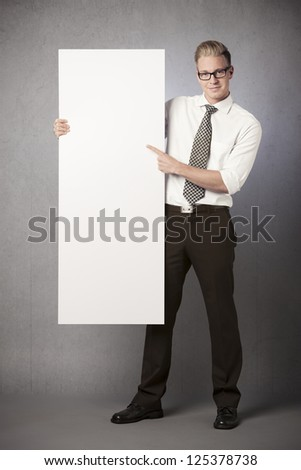 Friendly businessman holding and pointing finger at white empty vertical panel with space for text isolated on grey background. - stock photo