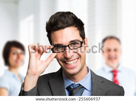 Friendly businessman portrait in front of his team