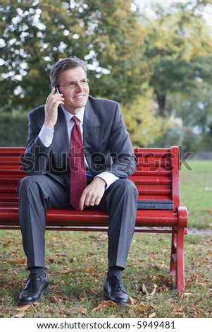 Friendly businessman with cell phone sitting on a red bench in a park - stock photo