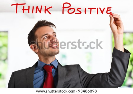 Friendly businessman writing a positive concept on the screen