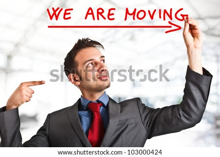 "Friendly businessman writing ""We are moving""on the screen - stock photo"