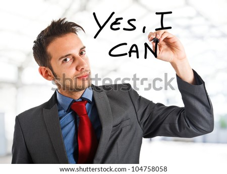 Friendly businessman writing Yes, I can on the screen - stock photo