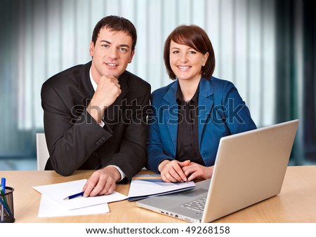 friendly businessteam is laughing into the camera - stock photo