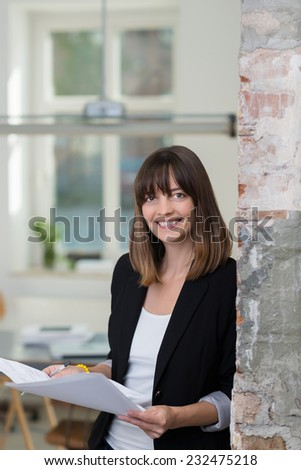 Friendly businesswoman smiling at the camera as she leans against a wall in the office reading a paper document