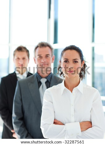 Friendly businesswoman with crossed arms in front of her team - stock photo