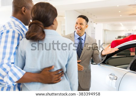 friendly car dealer showing new car to customers - stock photo