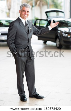 friendly car salesman doing welcoming gesture at car dealership - stock photo