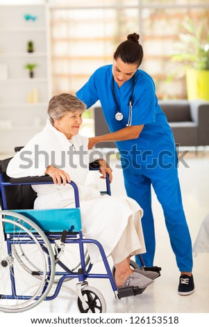 friendly caregiver helping senior woman on wheelchair - stock photo