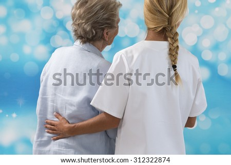 friendly  caregiver hugging senior patient outdoors -back view - stock photo