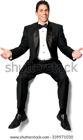 Friendly Caucasian man with short black hair in a tuxedo sitting with arms open - Isolated - stock photo