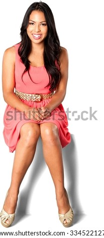 Friendly Caucasian young woman with long dark brown hair in evening outfit with hands on thighs - Isolated