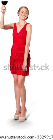 Friendly Caucasian young woman with medium blond hair in evening outfit holding wine glass and toasting - Isolated - stock photo