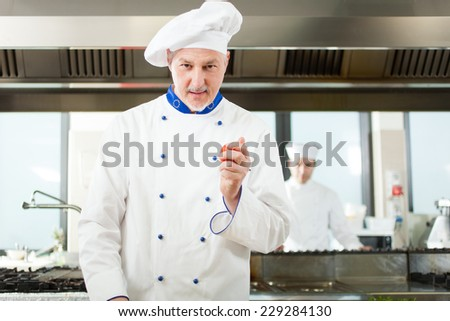Friendly chef holding a red tomato